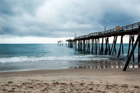 Old fishing pier in Frisco North Carolina outer banks left in ruins after a hurricane. Pier is destroyed and falling apart