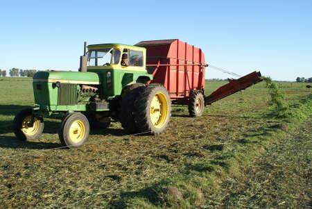 distributing: Tractor distributing fresh green pastures for livestock                 Editorial