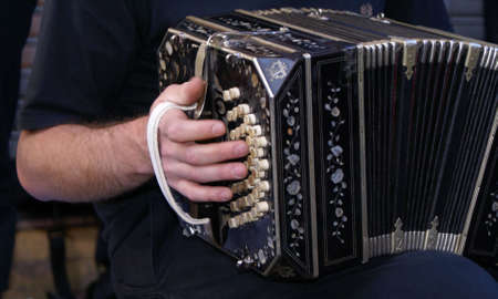 bandoneon: detail of a hand playing the bandoneon Stock Photo