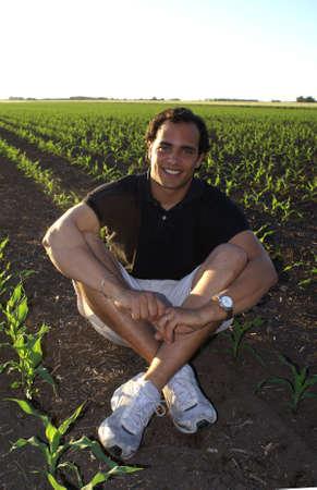 Dumny rolnik siedzi w polu kukurydziane              Zdjęcie Seryjne
