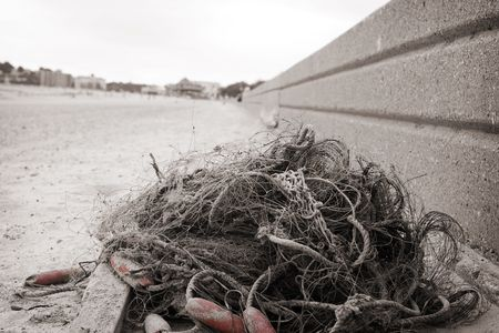 abandoned old fishing net lying on a beach Stock Photo - 7919790