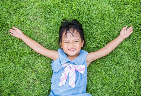 Asian little girl smile and lay on grass photo