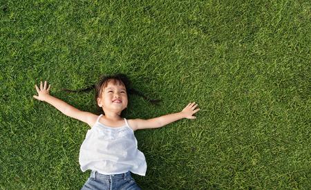 アジアの女の子の笑顔し、草の上に置く