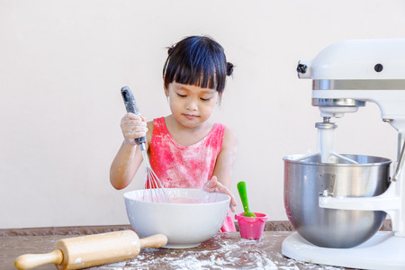 asian child: little chinese girl making bakery