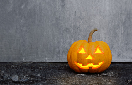 jack o lantern: halloween pumpkin on dirty wall scene Stock Photo