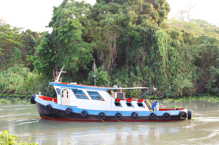 rainforest background: Tug boat in canal with rainforest background