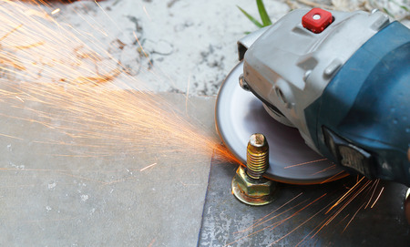 cutting metal: cutting metal bolt with grinder. Sparks while grinding iron
