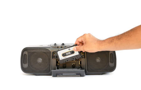 tape player: human hand putting tape into old-fashioned cassette tape player Stock Photo
