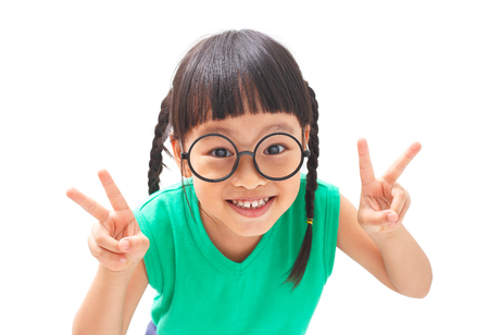 Happy little girl shows Victory sign with both hands Stockfoto