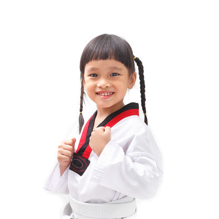 arts: Little child in taekwondo fighting action on isolated background