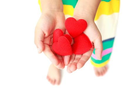 curare teneramente: Piccole mani in possesso di un cuore rosso Archivio Fotografico
