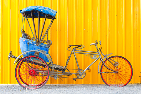 three wheeler: Vintage three-wheeler bicycle and yellow steel wall  background