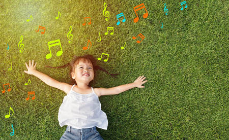 Asian little girl smile and lay on grass with music note background