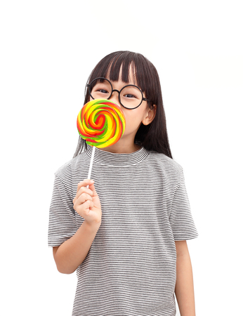 Asian little girl smile with colorful lollipop  isolated on white background Stock Photo