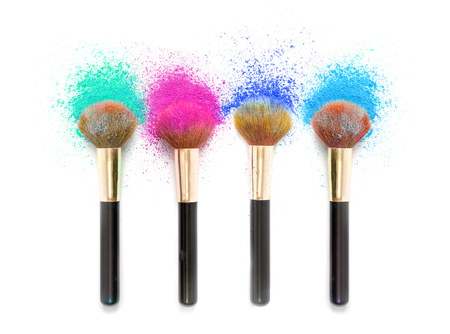 Cheek brushes with cosmetic powder color splash  and isolated on white background