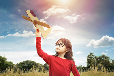 Little girl play paper plane with dreams of flight