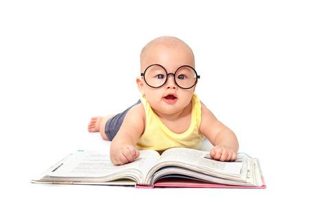작은 아기 크롤링 및 흰색 배경에 고립 된 큰 책을 읽고