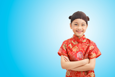 Chinese Little girl smile and wear cheongsam isolated on blue gradient background. Clipping path Stock Photo