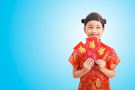 Chinese Little girl smile with red envelope and wear cheongsam isolated on blue gradient background. Clipping path