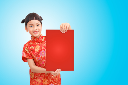 Chinese girl smile and wear cheongsam holding red board isolated on blue gradient background. Clipping path Stock Photo