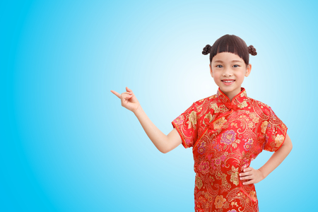 Chinese Little finger girl point acting and wear cheongsam isolated on blue gradient background. Clipping path