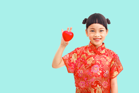 Chinese girl wear cheongsam with heart in hand isolated on blue background. Clipping path