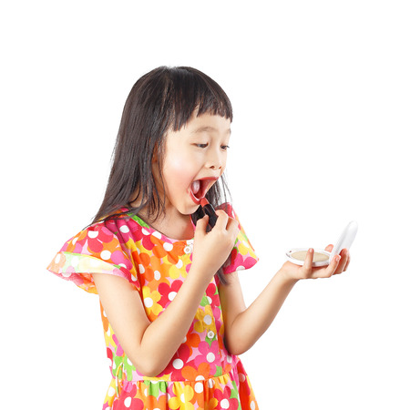 Little asian girl with red lipstick looking in mirror isolated on the white background. Stock Photo