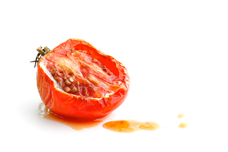 Rotten tomato with juice isolated on white background Stock Photo