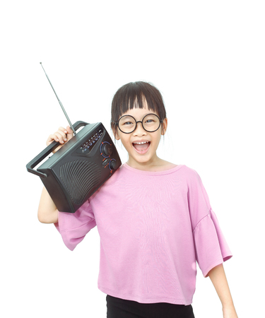 Little asian girl hold and listening music from a big radio Stock Photo