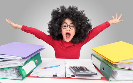 Asian young girl afro hair style sitting at a table in the office and screaming  among  a big stack job folder. Isolated on gray background