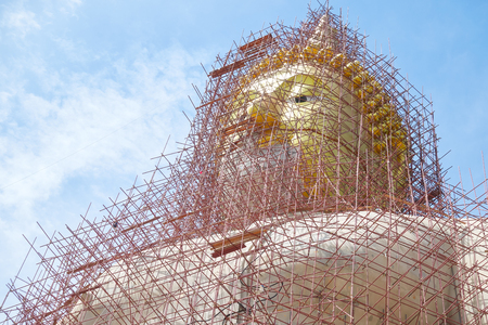 Big buddha statue under construction with many scaffolding,
