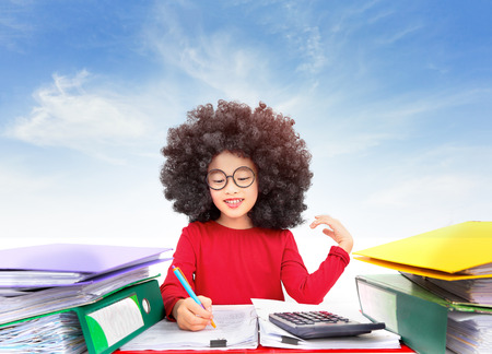 Asian young girl afro hair style sitting at a table in the office and writing at the information in the document with a big stack folder. sky background Stock Photo