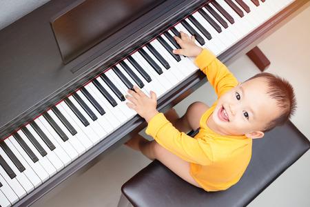 Baby boy happy to play piano.