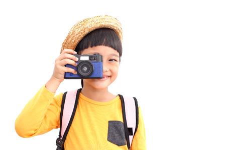 La muchacha feliz del viajero toma una foto con la cámara retro compack. Aislado sobre fondo blanco