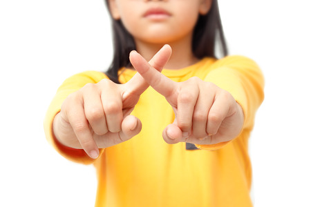 Little girl showing a cross finger for negative  sign meaning. Isolated on white background.