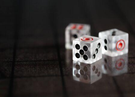 Transparent acrylic dice isolated on dark background 스톡 콘텐츠
