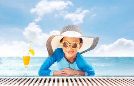 The little girl wears a big hat and a swimsuit. Smiling face with a background of sky and sea Banco de Imagens