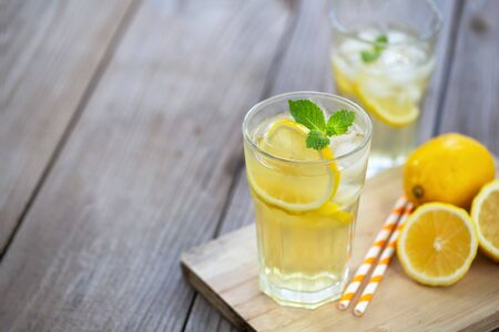 Lemonade with fresh lemon and mint leaves on the wood plank background Banque d'images - 131847179