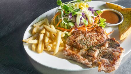 Pork steak with french fries on a white dish