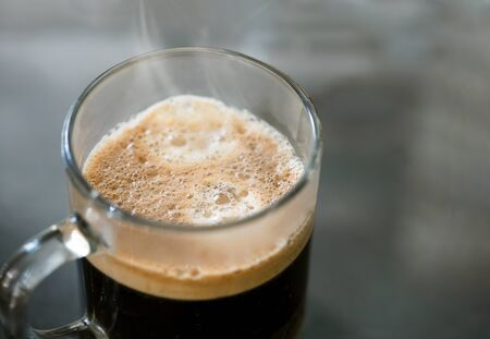 Espresso coffee in a glass mug. Isolated dark background. Stock Photo