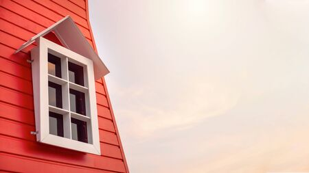 White window frame in a red houe with dusk sky background