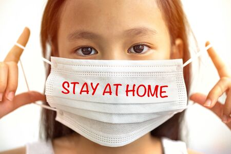 Asian girl wearing a mask with�Stay at Home�.