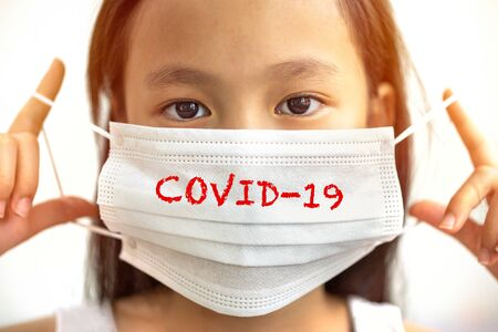 """Asian girl wearing a mask with """"covid-19� wording Stockfoto"""