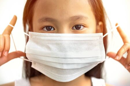 Asian girl wearing a mask close up and isolated from a white Stockfoto