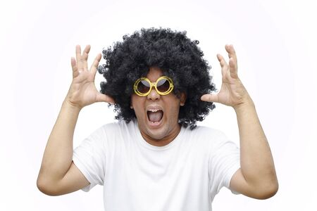 A man afro hair style is wearing a big yellow glasses with angry gesture. Stockfoto