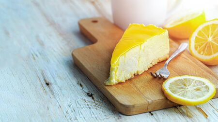 Lemon cheesecake is served on a wooden chopping board and slice of lemon beside.