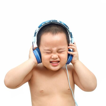 The little boy listens to music from the headphones. And with a very funny expression. Stockfoto