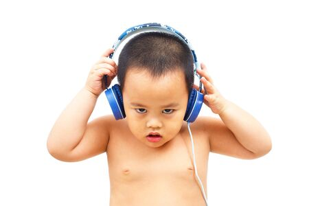 The little boy listens to rock music from the headphones. And with a serious expression.
