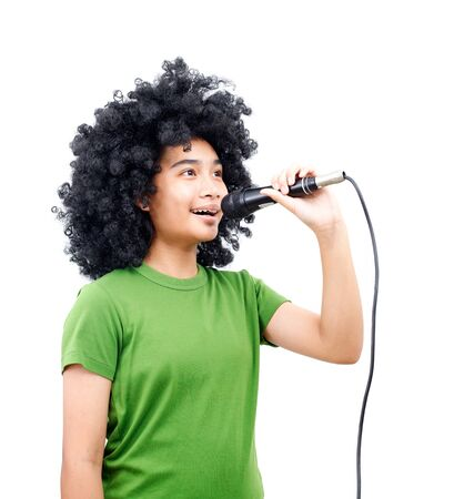 The Asian girl afro hair style is wearing a rgreen t- shirt, taking the microphone and sing a song. Isolated from white background Stockfoto
