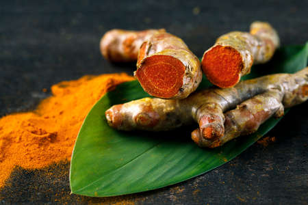 Fresh turmeric close up with turmeric powder isolated from dark background